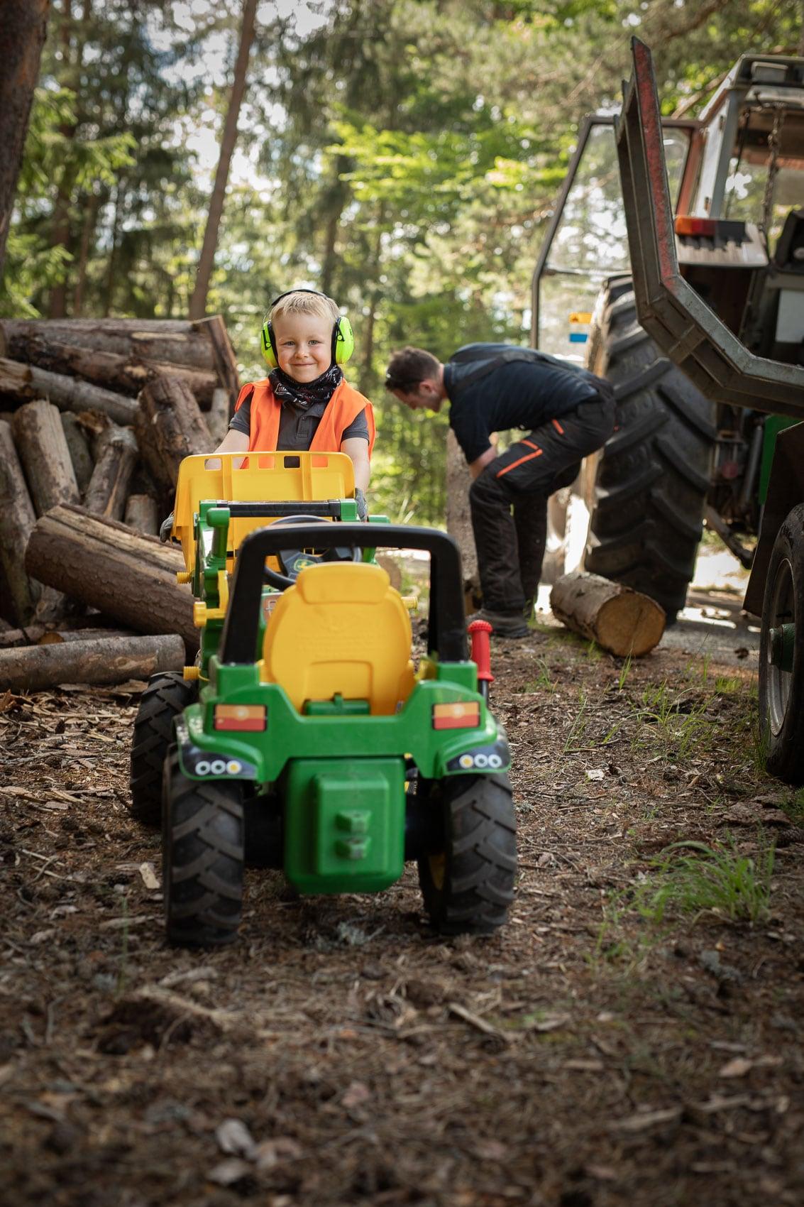 Kleiner Junge bei Holzarbeiten im Wald
